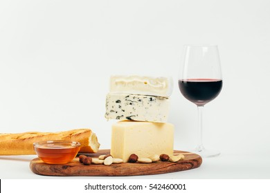 Still-life cheese platter with nuts, honey and red wine on white background