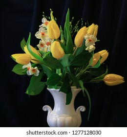 Still-Life with Elegant Spring Bouquet of Yellow Tulips, Narcissi and Fresh Green Branches in a White Classic Vase. Home Decor and Greeting Card Concept. Square Format