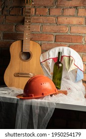 still-life with guitar, construction helmet and empty bottle
