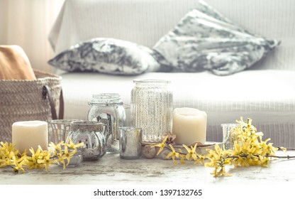 Still-life. Home cozy beautiful decor in the living room , a vase with spring flowers and candles on a wooden background , the concept of interior details