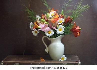 Still-life with a magnificent bouquet from bright lilies and gentle camomiles in a white jug