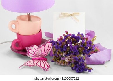 Still-life on a light background. Lamp, bouquet of wildflowers, butterfly and card.