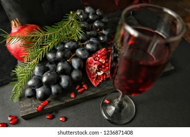 Still-life with pomegranates, fir branches, black grap and wineglass with red  wine on the background of a black wooden board