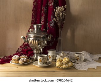 Still-life in Russian style with an old samovar, tea in cups, biscuits and cakes on a wooden table close-up