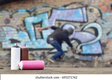 A still-life of several aerosol paint spray cans lies on a roofing covering on the background of a brick wall, on which is painted a bright and colorful graffiti drawing. Items related to street art