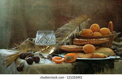 Still-life, tasty breakfast pies with cheese and a glass of white wine with juicy fruit