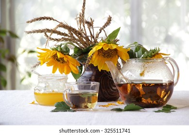 Still-life with tea in a transparent teapot and a bouquet of sunflowers