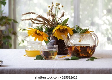 Still-life with tea in a transparent teapot, honey and a bouquet of sunflowers