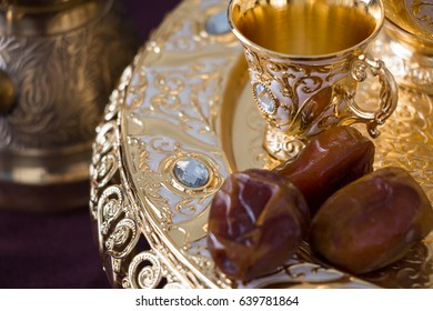 Still-life with traditional golden arabic coffee set with dallah, coffee pot (jezva), cup and dates. Dark background. Horizontal photo
