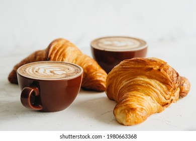 Stilllife of two cups of cappuccino and two croissant on white table
