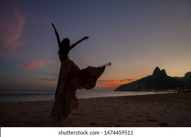 Stilt dancer on the sands of Ipanema-Rio de Janeiro beach in a beautiful and colorful sunset that created an incredible silhouette. Dois Irmãos Hill and waters of the Atlantic Ocean in the background.