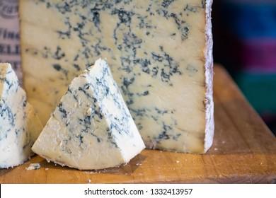 Stilton cheese on wooden board on display at Artisan food market