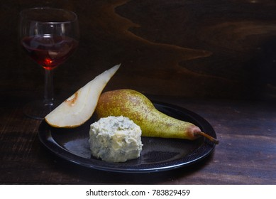 stilton cheese, pears and red port wine on a dar rustic wooden background, copy space, selected focus, narrow depth of field