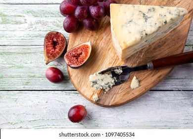 Stilton on a cheese board with red grapes and cheese spoon, top view