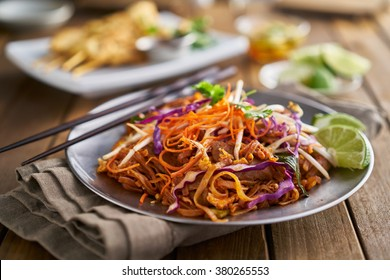 stir fried beef pad thai with color garnish and chopsticks