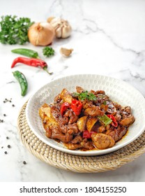 Stir Fried Blackpepper Chicken with Fried Potatoes. Asian foods. Served on white bowl with white background.