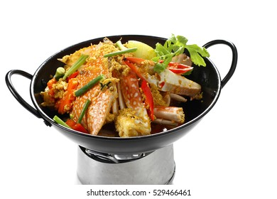 Stir fried Blue Swimming Crabs (Portunus pelagicus) with Yellow Curry Powder in Black Pan Isolated on White Background, Top Front View. Popular Thai Food. Selective Focus at the front.