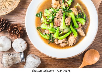 Stir fried Chinese cabbage ( Bok Choy green vegetable ) with pork , garlic and soy sauce in white dish on table, cooked, ready to serve.