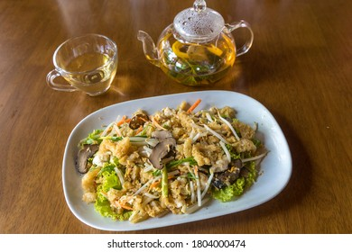 Stir fried fish maw. Stir fried fish maw in a white plate on a wooden table. Fried fish maw add shiitake,stir fry fish maw with egg and vegetable in Chinese style