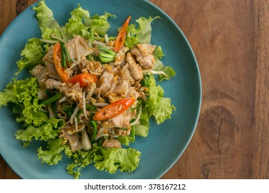 Stir fried Flat Rice Noodle with Soy Sauce and Pork 'Pad See Eww' on wooden table - Thai street food