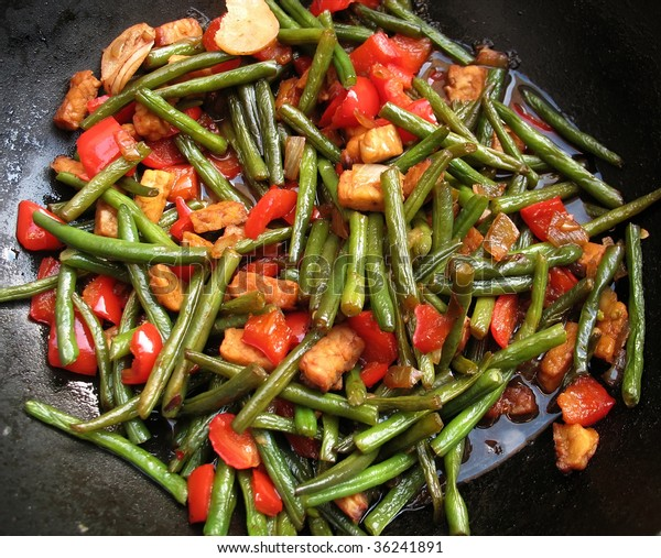 Stir fried green beans with red pepper, ginger and tempeh in black wok, tumis boentjes