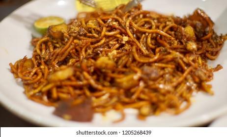 Stir fried noodle or mee goreng mamak or mi goreng, asian famous food with fried egg. Selective focus.
