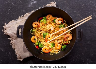 Stir fried noodles with shrimps and vegetables in a wok on dark table, top view