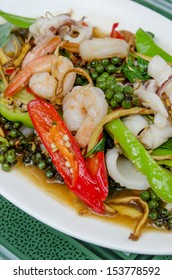 stir fried  seafood  with herbs and mix vegetable on white dish