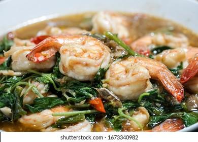 Stir fried shrimp with basil on a white plate. Thai food.