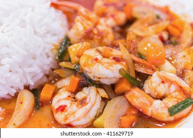 stir fried shrimp in thai red curry paste with rice and fried egg , Spicy Fried Shrimp , Curry fried shrimps and cooked rice in white dish closeup on table , Fried stir shrimp with red curry
