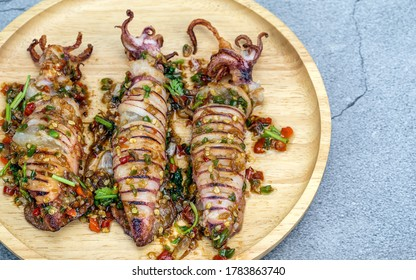 Stir Fried Squid with Salt and Pepper In a wooden plate placed on a cement ground
