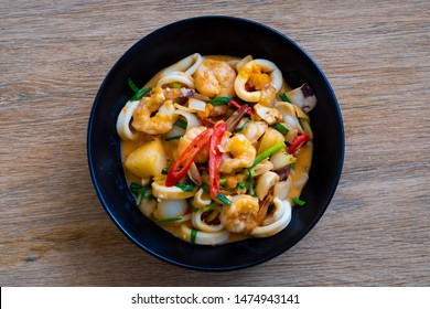 Stir Fried Squid with Salted Eggs on black plate on wooden table , Thai food.
