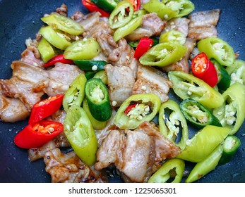Stir fried streaky pork with chilli peppers sliced in non-stick pan