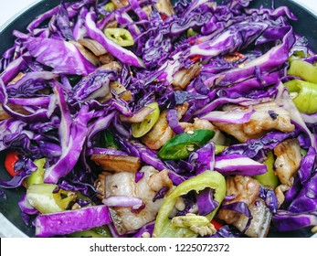 Stir fried streaky pork with purple cabbage and chilli peppers sliced in non-stick pan