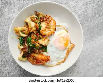 Stir fried thai basil with shrimp, squid and a fried egg.