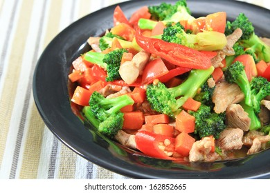 stir fried vegetables with pork in red dish.