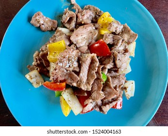 Stir fried venison with black pepper on a blue plate