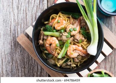 "Stir fried yellow noodle ""mee pad hokkian phuket"" rice yellow noodle with soy sauce, prawn, pork, oyster and egg. Thai food phuket"