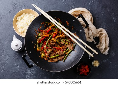 Stir fry beef meat with vegetables and rice in wok pan on dark stone background