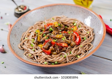 Stir fry from chicken hearts, paprika, onions and buckwheat noodles