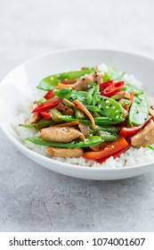 stir fry chicken and vegetables with rice in white bowl, selective focus