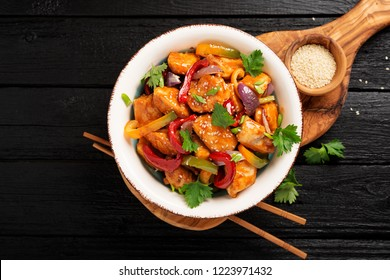 Stir fry with chicken, vegetables, soy sauce and sesame on black wooden background.