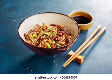 Stir fry with noodles and beef garnished with sesame seeds in bowl. Traditional asian cuisine. Soba noodles, asian cuisine