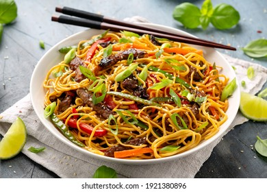 Stir fry noodles with beef and vegetable in white bowl. asian style food