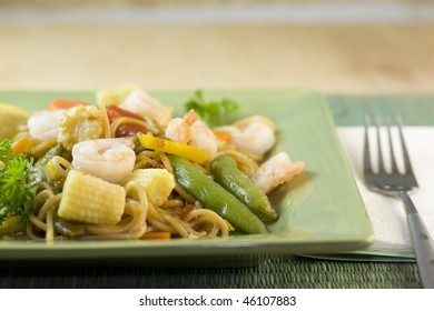 stir fry noodles with shrimp, snap peas, baby corn on a green plate