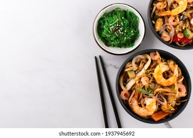Stir fry noodles with shrimps and mussels in a black bowl and seaweed salad on a white stone background, top view, copy space.