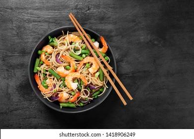 Stir fry noodles with shrimps and vegetables in black bowl.