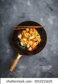 Stir fry noodles, traditional Chinese wok, chopsticks. Asian noodles with vegetables, chicken. Wok noodles, Chinese dinner/lunch. Rustic stone background. Top view. Asian/Chinese noodles. Stir frying
