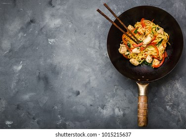 Stir fry noodles in traditional Chinese wok, chopsticks, ingredients. Space for text. Asian noodles with vegetables, chicken. Wok noodles. Rustic stone background. Top view. Asian/Chinese dinner
