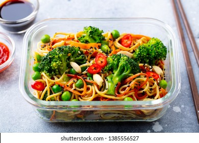 Stir fry noodles, udon with vegetables in lunch box. Grey stone background. Close  up.